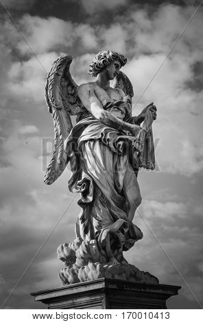 Black and white statue of The Angel Carrying the Scouragel  on the bridge leading to the Castle Sant'Angelo, Rome. Designed by Bernini for Pope Clement IX.