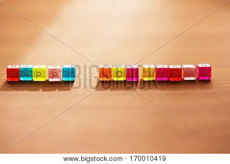 Happy Holidays. Colorful alphabet cubes aligned sideways on a table with in coming light. Extremely shallow depth of field.