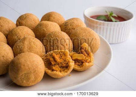 Indian special traditional fried food dry fruit Kachori which is small and round in shape, with tomato sauce and hot tea, Haldiram product