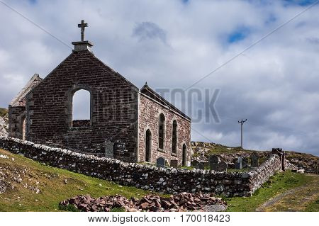 Assynt Peninsula Scotland - June 7 2012: Roofless ruins of Parliamentary Church with small cemetery and historic tomb stones. Brown-reddish stones. Blue sky with white clouds. Green grass.