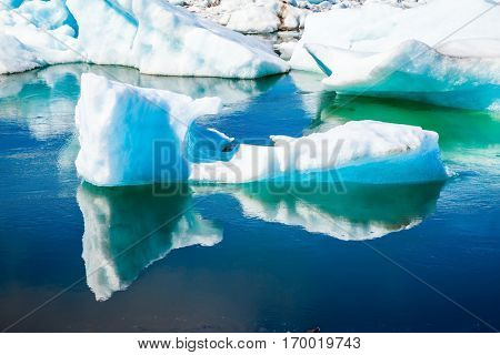 Gorgeous morning light in the Ice Lagoon. Drift ice Ice Lagoon - Jokulsarlon. Icebergs and ice floes are reflected in the smooth water surface. The concept of extreme northern tourism