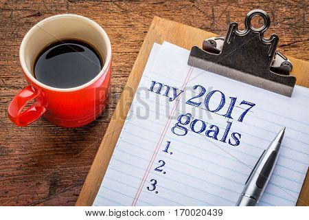 my 2017 goals list on clipboard and coffee against grunge wood desk