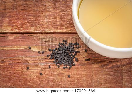 black cumin seeds (Nigella sativa) and oil in a small bowl against rustic bran wood
