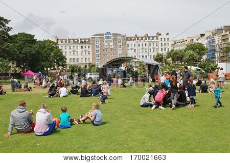 ST. LEONARDS-ON-SEA, ENGLAND - JULY 9, 2016: People sit on the grass during the annual St. Leonards Festival. The community music and entertainment event was first held in 2006.