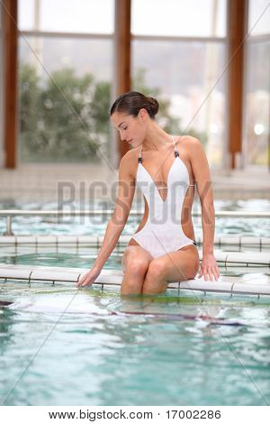 Beautiful woman laying by a thalassotherapy pool