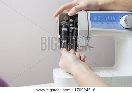 Master repairing white sewing machine