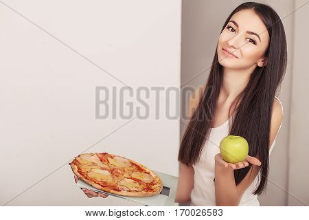 Diet And Fast Food Concept. Overweight Woman Standing On Weighing Scale Holding Pizza. Unhealthy Junk Food. Dieting, Lifestyle. Weight Loss. Obesity.