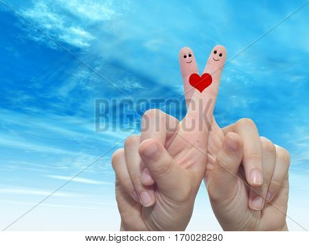 Concept or conceptual human or female hands with two fingers painted with a red heart and smiley faces over cloud blue sky background  for valentine, romantic, love, couple, young, family or wedding