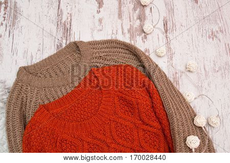 Two knitted sweaters on a wooden background. Garland of rattan lanterns. Fashionable concept closeup