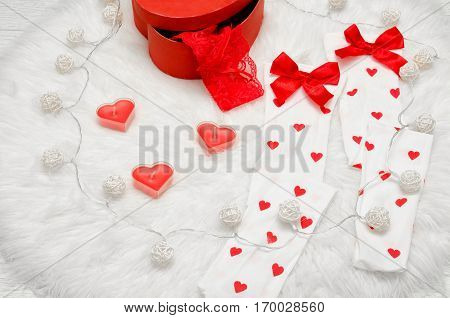 Fashion concept. Candles in the shape of heart white stockings with bow red box with lacy linen white fur. Garland of lanterns