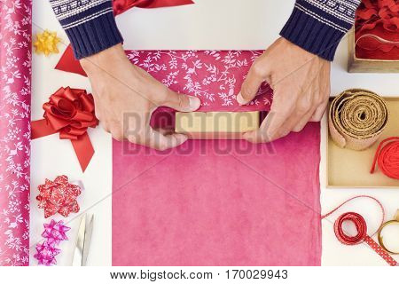 high-angle shot of a young caucasian man wrapping a gift on a white table full of boxes, wrapping paper with different patterns and strings and ribbons of different colors