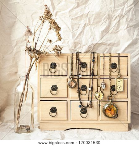 Some old vintage pocket watches on a wooden jewelry storage box time concept. Retro still life - dry wild flowers and wooden chest of drawers for woman beauty