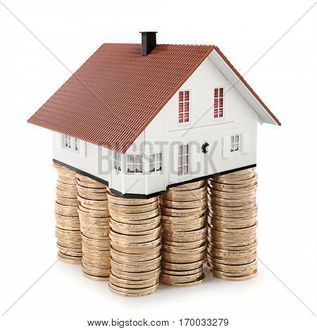 House at the top of stack of coins as concept related to real estate business.