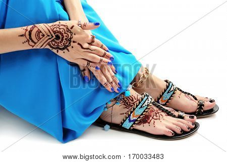 Female legs and hands with henna tattoo on white background