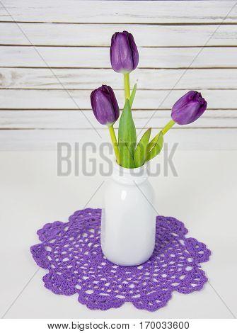 purple tulip bouquet in retro milk bottle on doily
