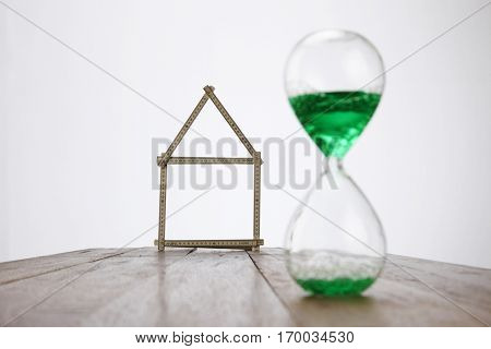 model house and hour glass on the white background
