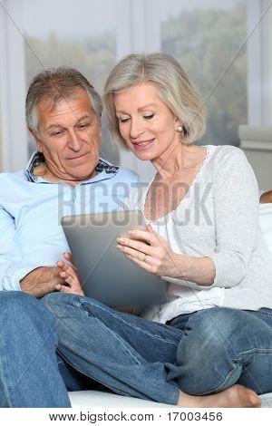 Senior couple surfing on internet with electronic tablet