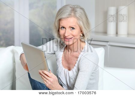 Closeup of senior woman sitting on sofa with electronic pad