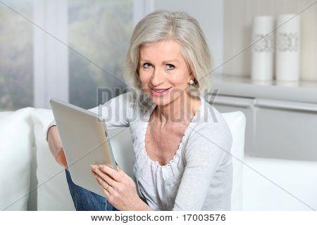 Closeup de senior mujer sentada en el sofá con pad electrónico