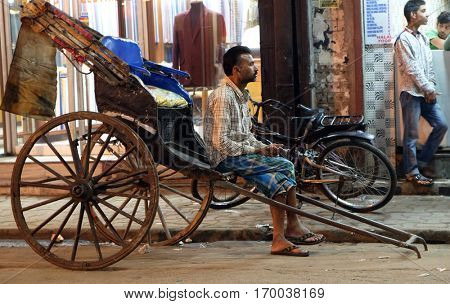 KOLKATA, INDIA - FEBRUARY 09: A hand rickshaw puller waits for passengers in his rickshaw in Kolkata on February 09, 2016.