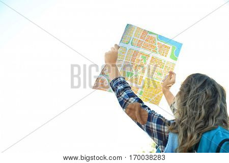 Young woman searching direction on map