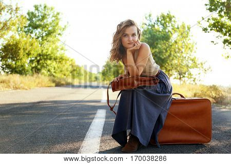 Beautiful young woman sitting on suitcase in middle of road