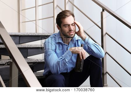 Tired office worker sitting on stairs with bottle of beer
