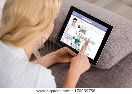 Close-up Of Young Woman On Couch Using Social Networking Site On Digital Tablet