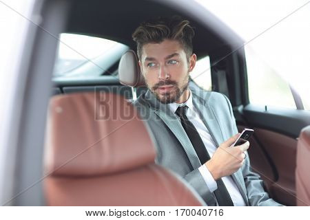 Happy young businessman using mobile phone in back seat of car