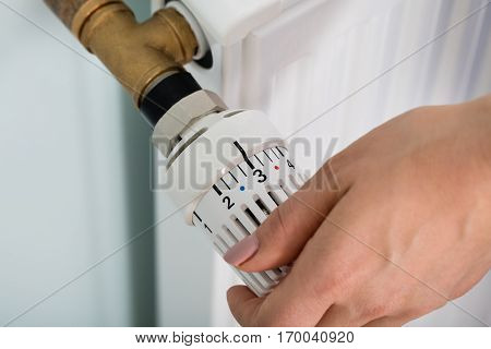 Close-up Of Woman's Hand Adjusting Radiator Thermostat Valve At Home
