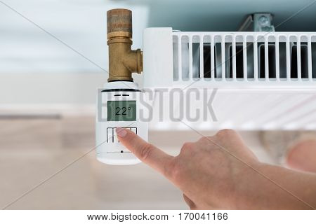 High Angle View Of Person Hand Adjusting Temperature On Thermostat
