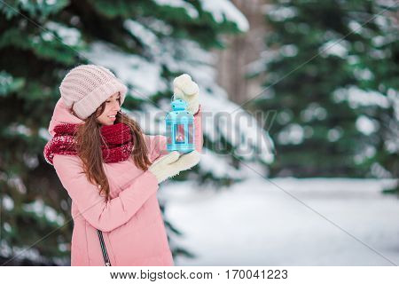 Young woman holding Christmas candlelight outdoors on beautiful winter day