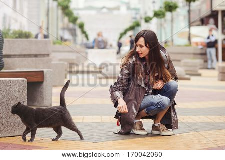 Beautiful Woman Walking With A Cat In The City