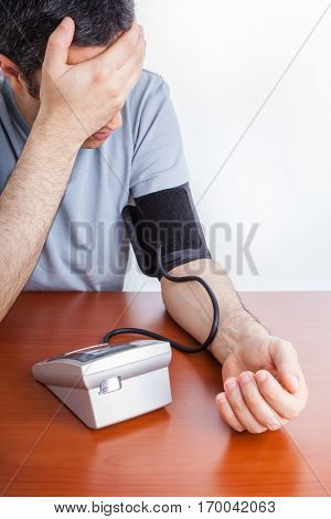 Man feeling sick and checking the blood pressure