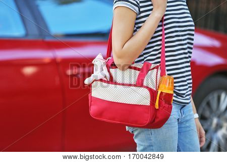 Woman with baby bag standing near a car