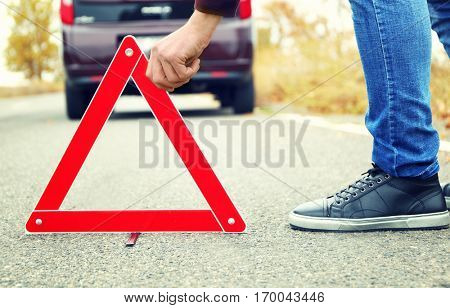 Driver putting out a traffic warning sign on road