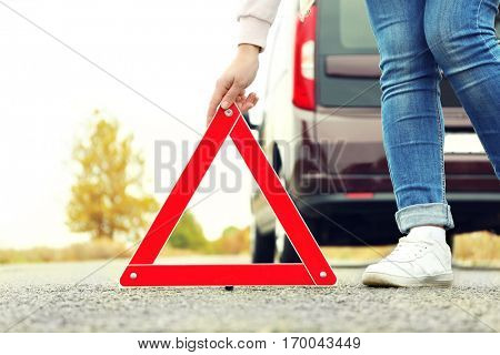 Female driver putting out traffic warning sign on road
