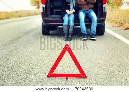 Traffic warning sign on road with car and couple on background