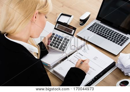 High Angle View Of A Accountant Businesswoman Calculating Invoice Using Calculator In Office