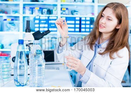 Woman science Assistant in laboratory with test of drink water