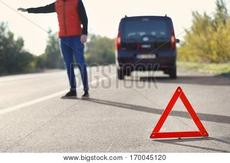 Red warning triangle on asphalt road. Driver catching car on road