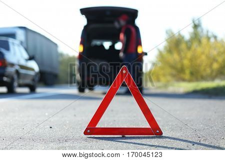 Red warning triangle on asphalt road. Emergency stop concept