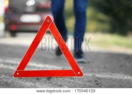 Close up view of red warning  triangle on asphalt road. Emergency stop concept