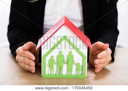Businesswoman Protecting House Model With Papercut Family House On Wooden Desk