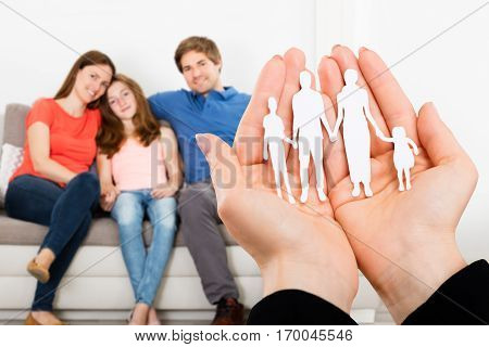 A Person Hand Holding Family Papercut In Front Of Family Sitting On Sofa At Home