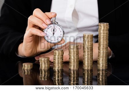 Businesswoman Showing Stopwatch In Front Of Stacked Coin On Desk. Quick Money Concept