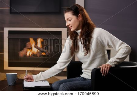 Young woman sitting at home at fireplace in armchair, writing notes in notebook, looking down.