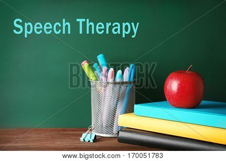 School stationery on wooden table. Text SPEECH THERAPY on chalkboard background