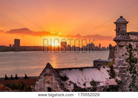 Beautiful sunset in Havana with a view of the city skyline and the sun setting over the buildings - Seen from an El Morro castle across the bay
