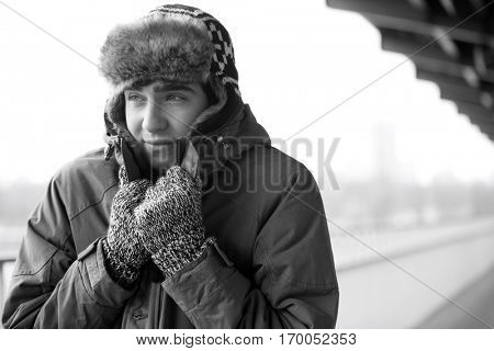 Man in warm clothing shivering outdoors